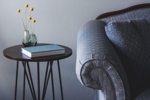 Bild Beistelltisch mit Buch und Couch daneben