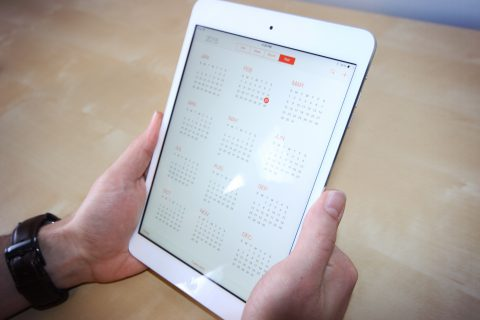 Bild Hände halten Tablet mit Kalender-Oberfläche